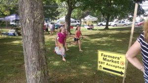 Children participate in the Union Farmers' Market's kids' scavenger hunt, a program that also operates out of the market information booth where SNAP customers pick up a shopping sheet and receive their Maine Harvest Bucks.